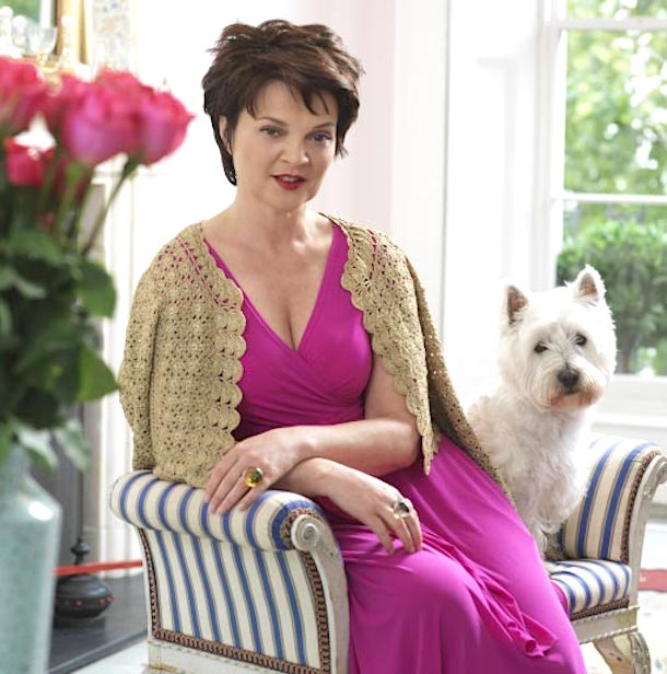 Lulu Guinness in pink dress beside her Westie dog on striped chair